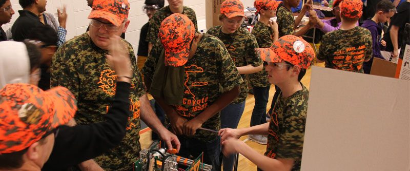 LOGICoyote team members work on a robot at a competition