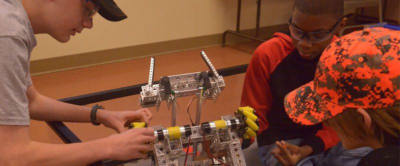 Various team members work on their robot