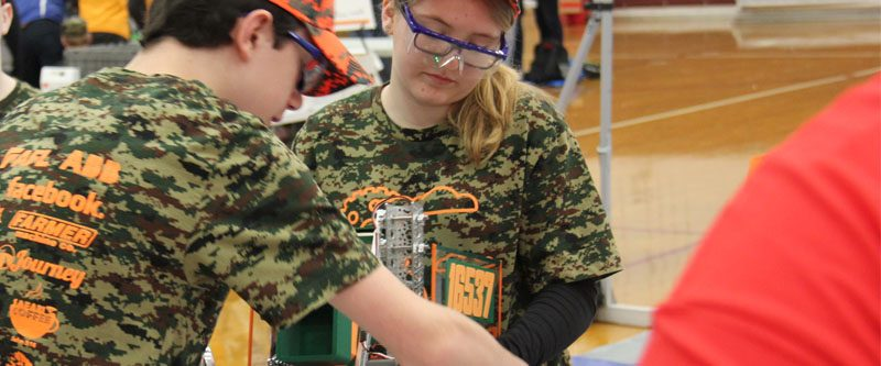 Team members Lydia and Michael deliver their robot for inspection